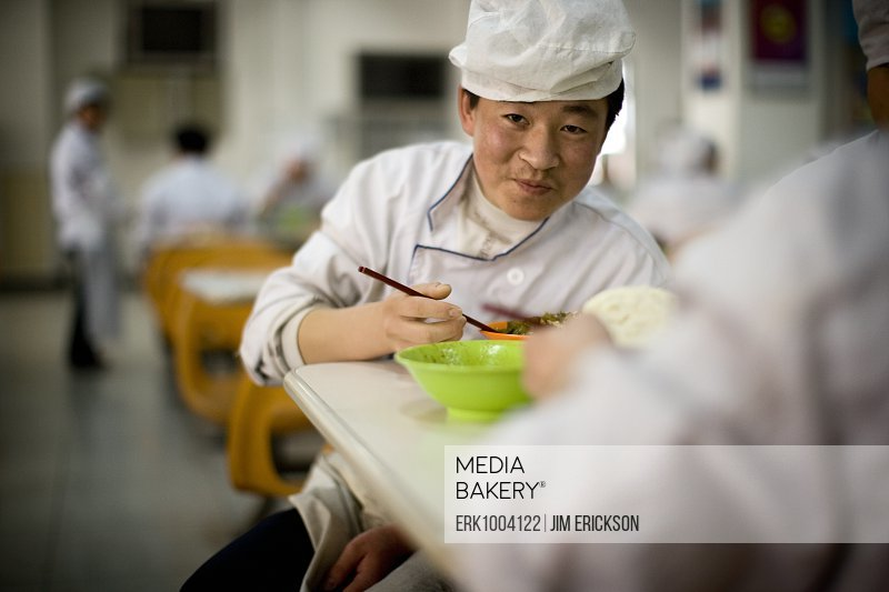 Portrait of a mature male chef eating food in a canteen.