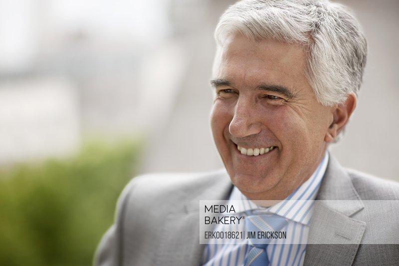 Mature businessman laughs as he poses for a portrait outside.