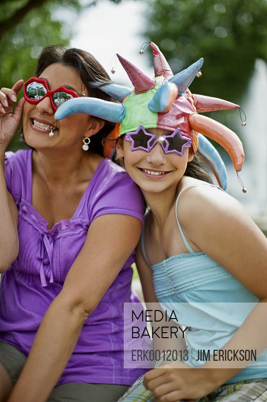 Smiling mother and daughter wearing novelty hats and sunglasses.