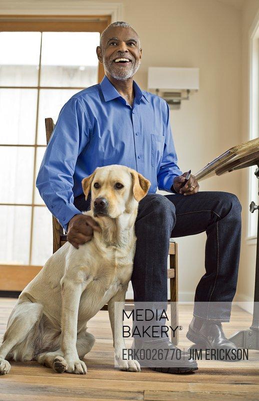SMiling man sits and pats dog