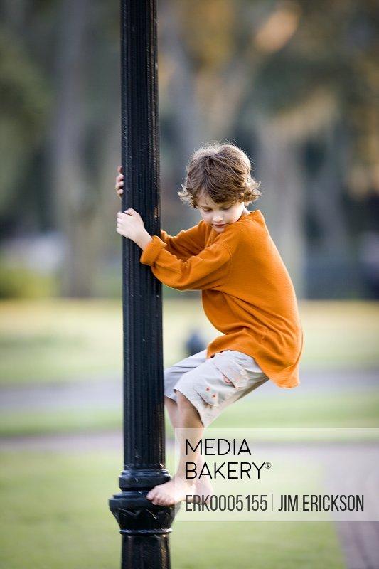 Boy climbing a street light.