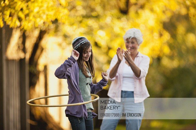 Senior woman watches her granddaughter hula hooping.