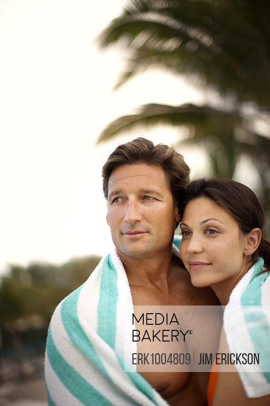 Content mid adult couple wrapped in a towel together.
