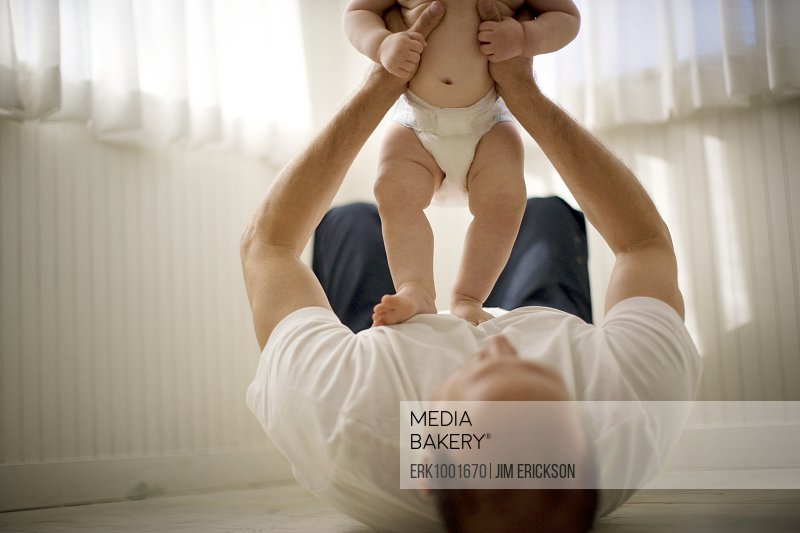 Mature man lying down while playing with his baby son.