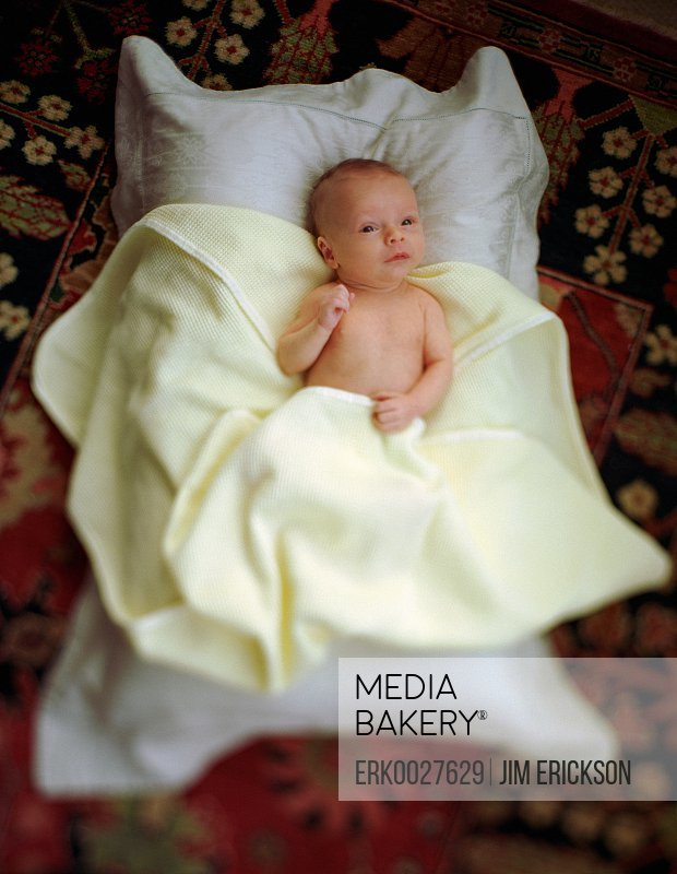 Baby on pillow with yellow blanket,