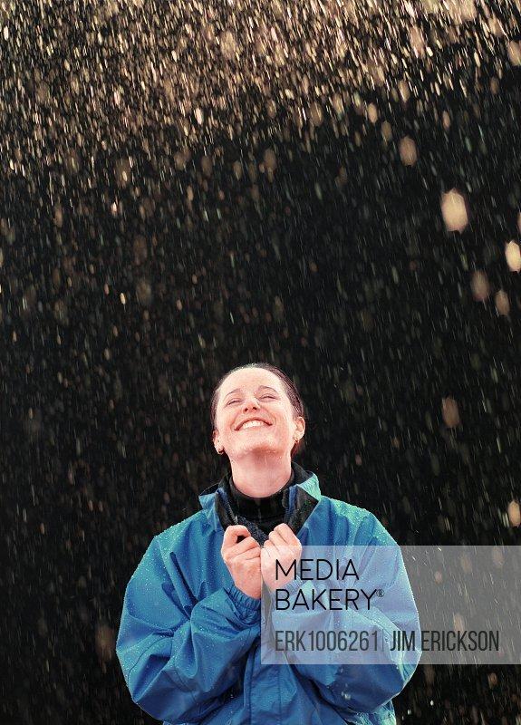 A young woman enjoys a snowfall outside.