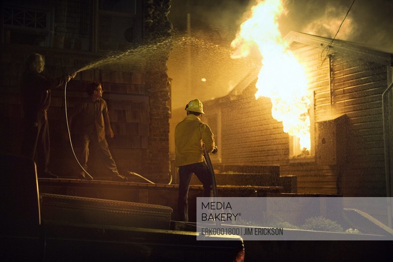 Two individuals extinguishing a house on fire.