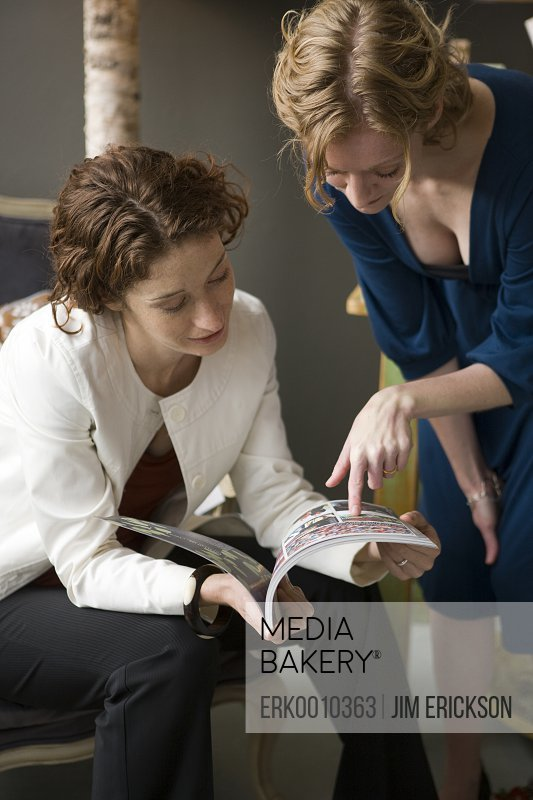Two women reading a book.