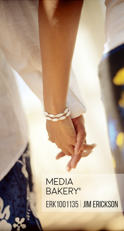 Mid adult couple holding hands.