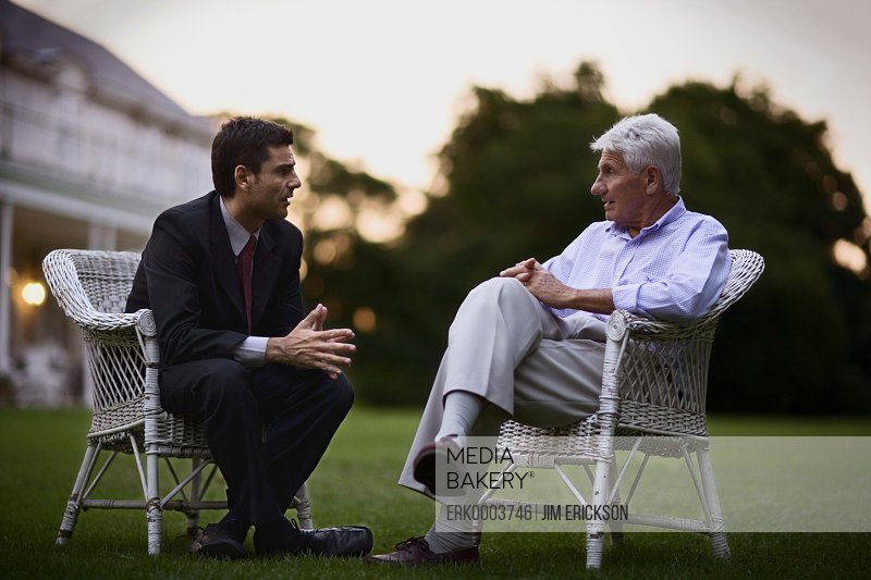 View of two gentlemen in formal attire having a conversation.