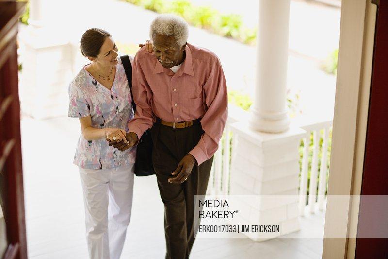 Young nurse helps her elderly patient to walk.