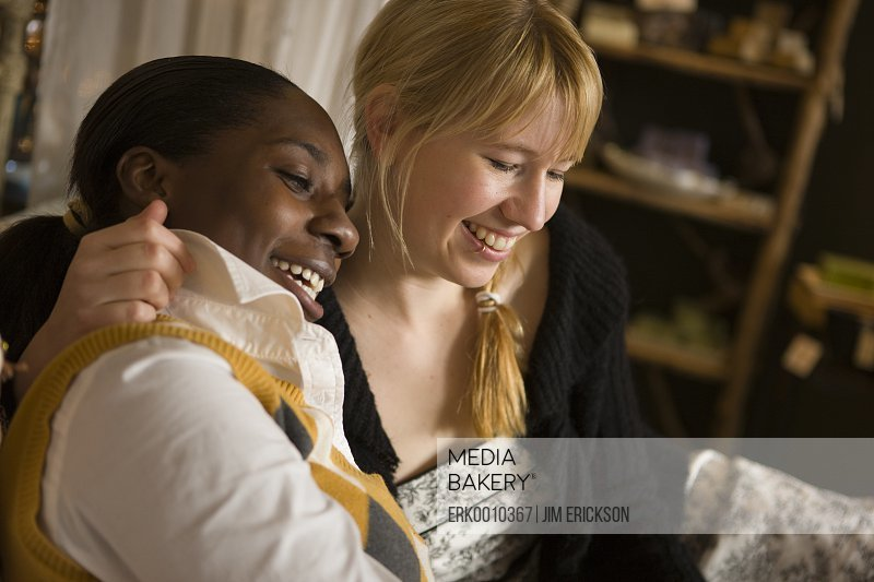 Two smiling women sitting together.