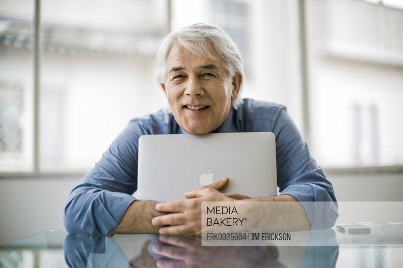Content mature businessman hugging his laptop computer.