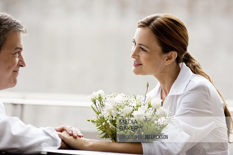 Businesswoman receiving flowers from her husband.