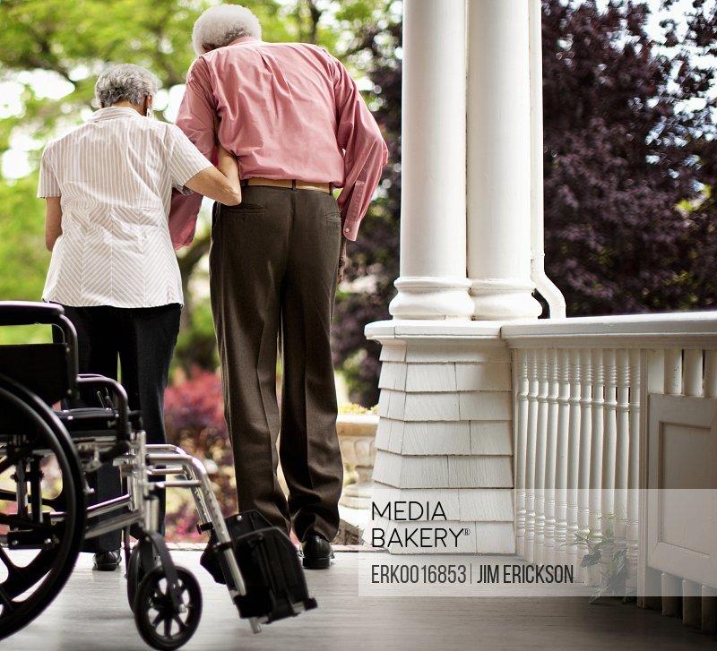 Elderly woman assists her husband walk.