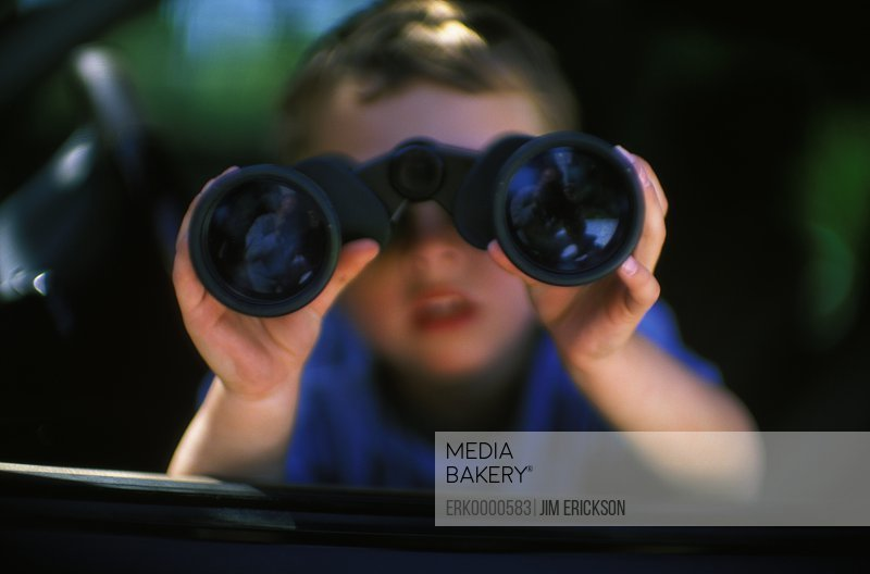 Pair of binoculars being looked through by a young boy.