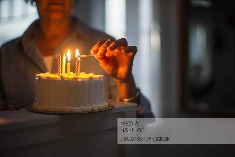 Hand of a mature woman lighting a candle on a birthday cake.