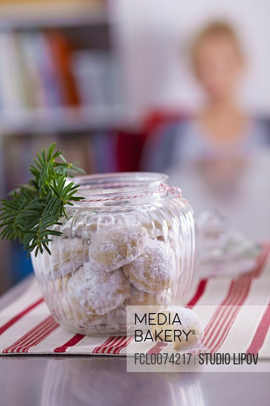 Butter biscuits in a storage jar with a sprig of fir/n