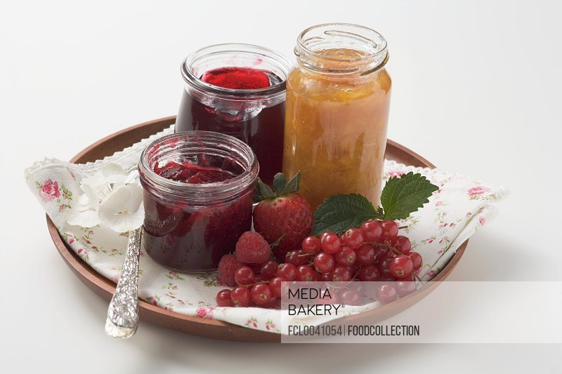 Jars of jam and fresh berries on tray
