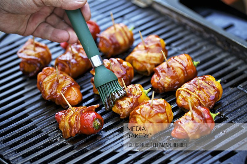 Stuffed mini peppers wrapped in bacon on a barbecue