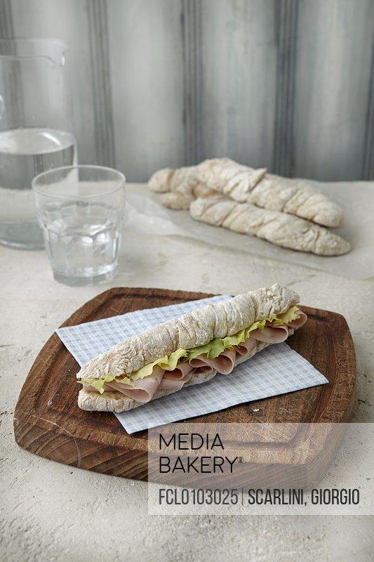 A mini baguette with mortadella and lettuce