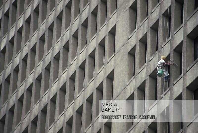 Window washer dangling precariously on side of tall office building washing windows