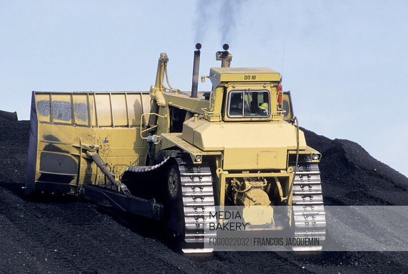 Large digging or bulldozing equipment moving large pile of earth
