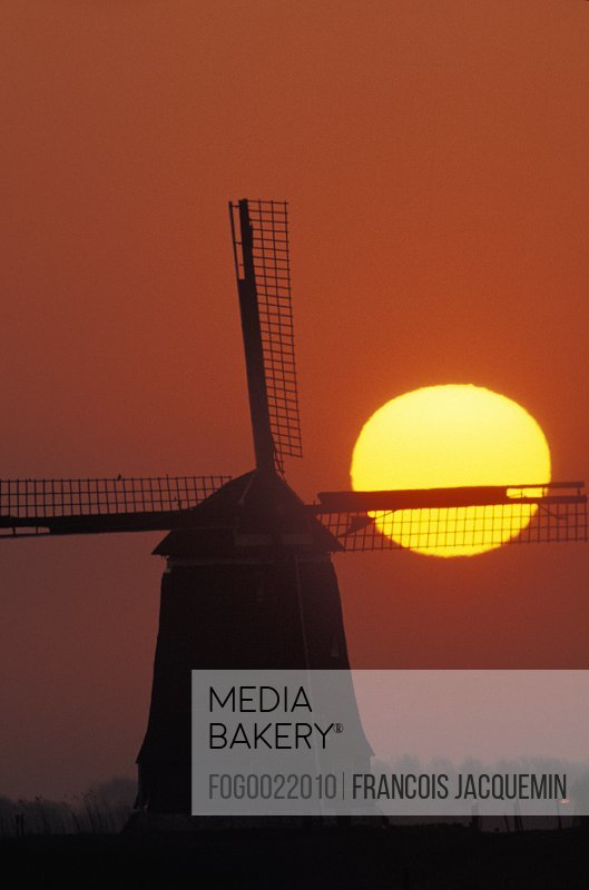 Silhouette of old-fashioned, wooden windmill with yellow setting sun in background