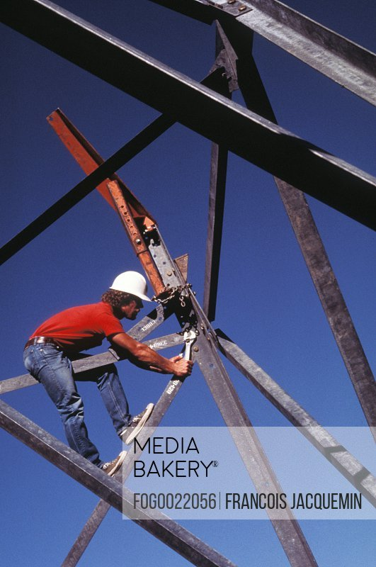 Construction worker on construction site balanced on girder using wrench to tighten metal supports