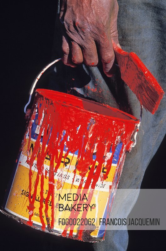 Close up of man's hand holding paintbrush and tin can of red paint