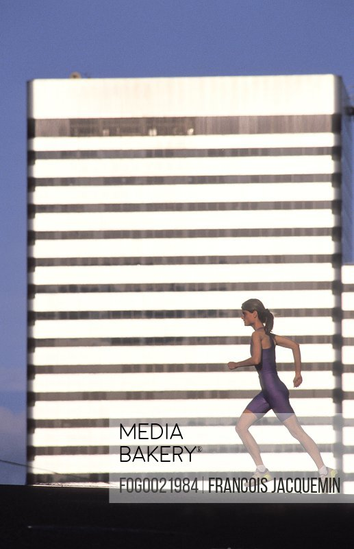 Determined, athletic runner in sportswear running in urban area with highrise in background