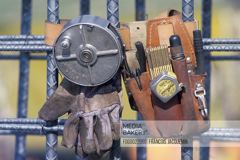 Close up of construction worker's equipment gloves, tool belt, measuring tape, pliers