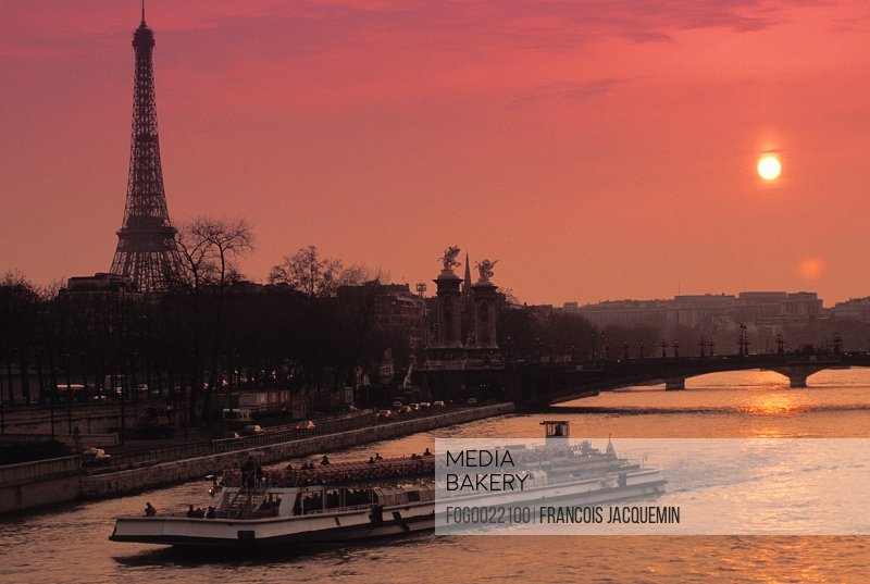 Tourist boat on river in Paris with sunset in background, France