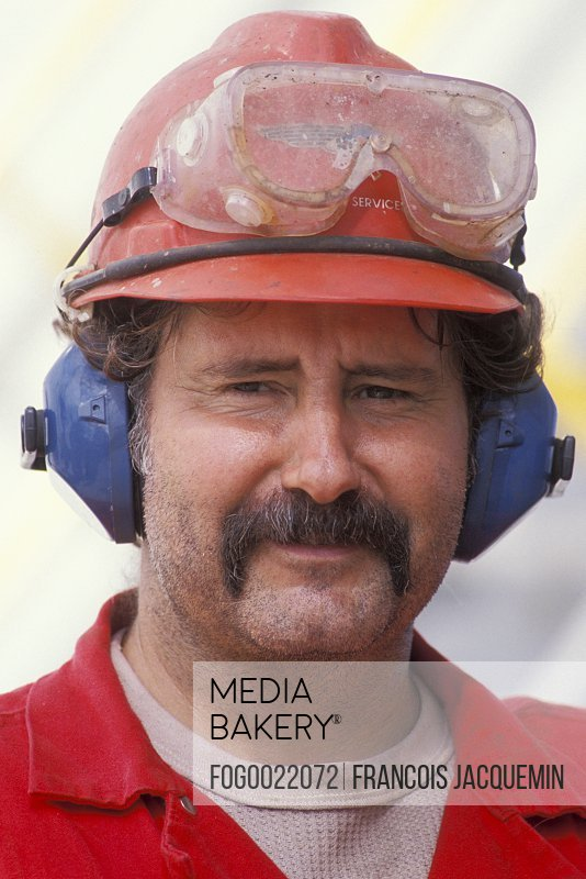 Smiling, mature construction worker with mustache in eyeglasses, hard-hat and headphones