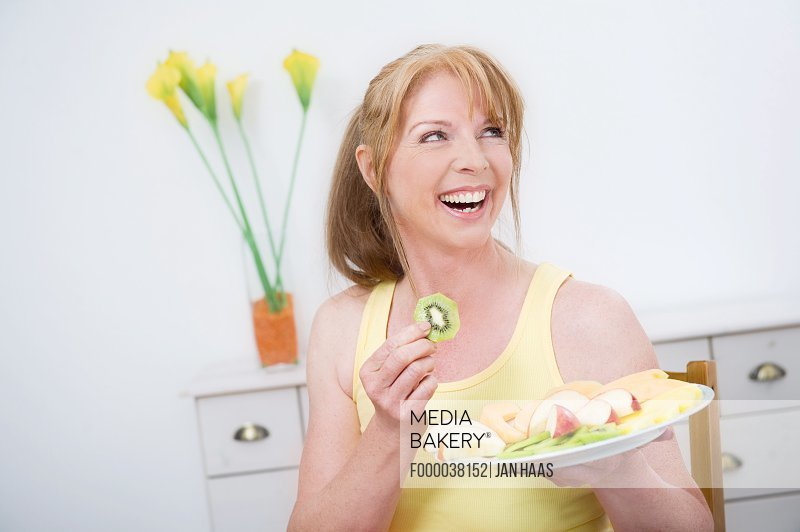 Woman holding assorted fruits on plate