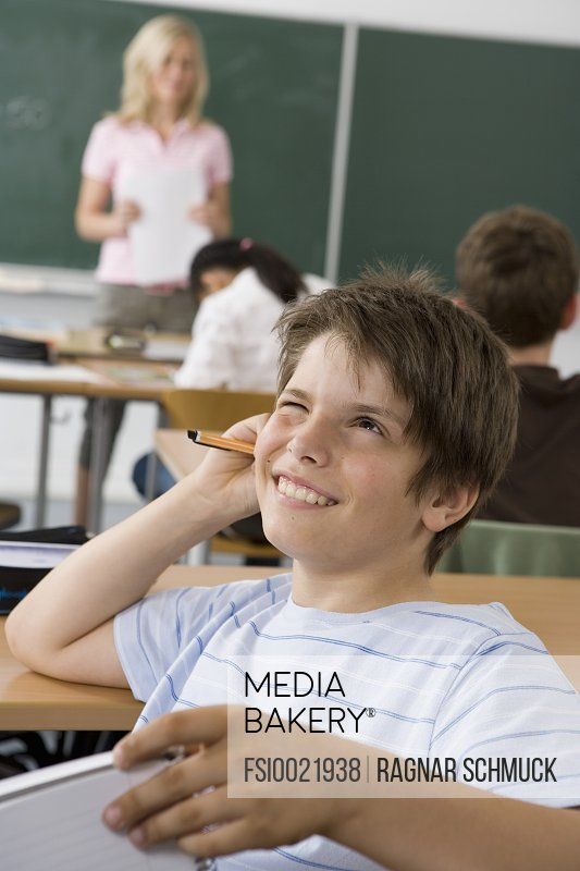 A pre-adolescent boy sitting in the back of a classroom, looking up in contemplation