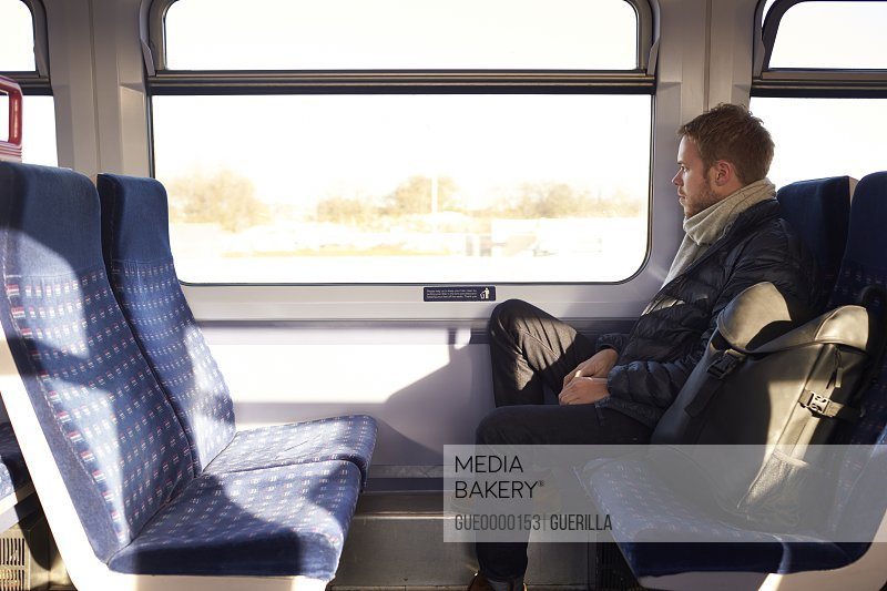Young Man Sitting In Train Carriage On Railway Journey
