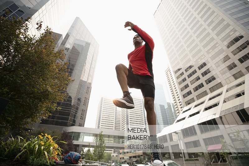 Athletic male runner on the move below city highrise buildings