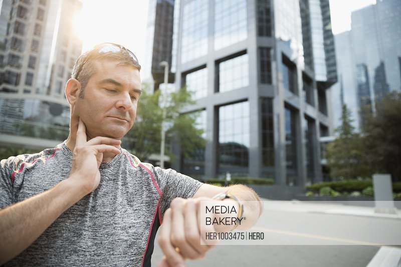 Male runner checking pulse with smart watch on urban street