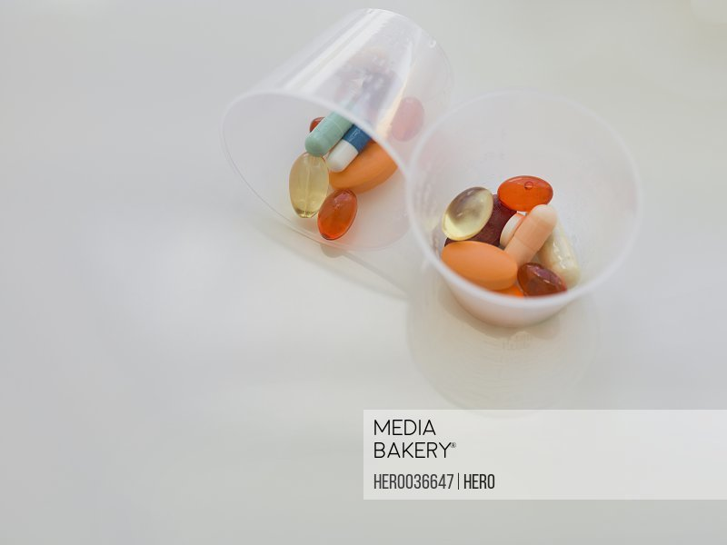 Cups containing various medication and capsules