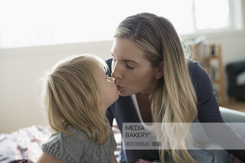 Affectionate blonde mother and toddler daughter kissing