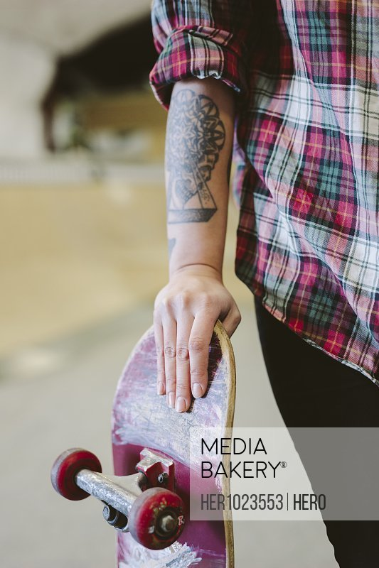 Young female skateboarder with tattoo