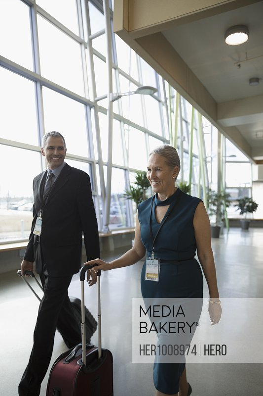 Businessman and businesswoman walking with suitcases in office lobby