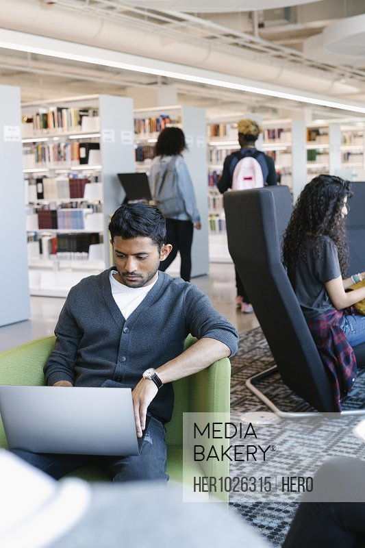 Student sitting in library and using laptop