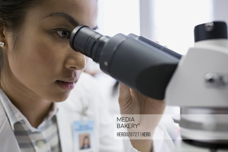 Close up focused medical scientist using microscope