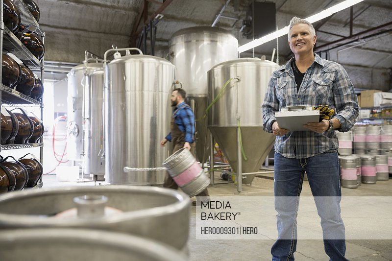 Brewery worker with clipboard near vats and kegs