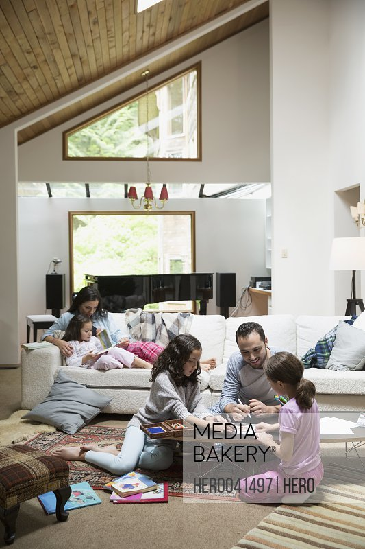 Father coloring with daughters in living room