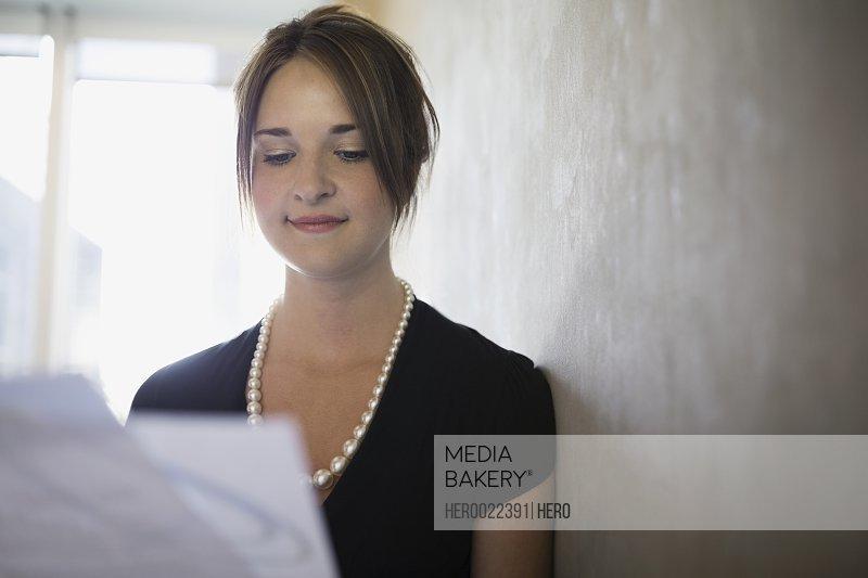 Businesswoman reading paperwork along wall