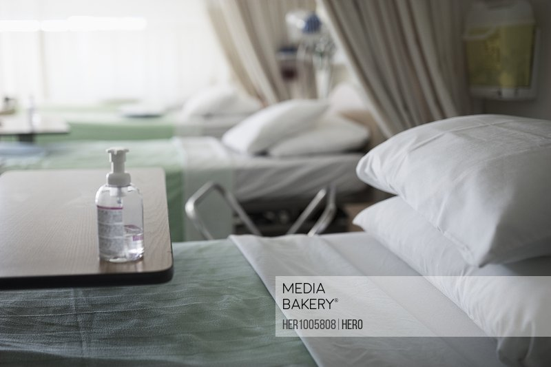Antibacterial bottle on tray over hospital bed