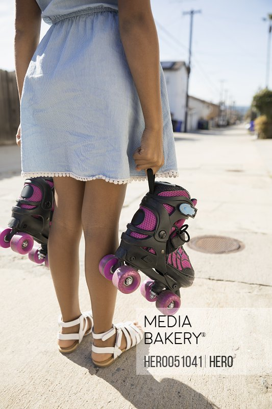 African American girl holding roller skates on sunny road